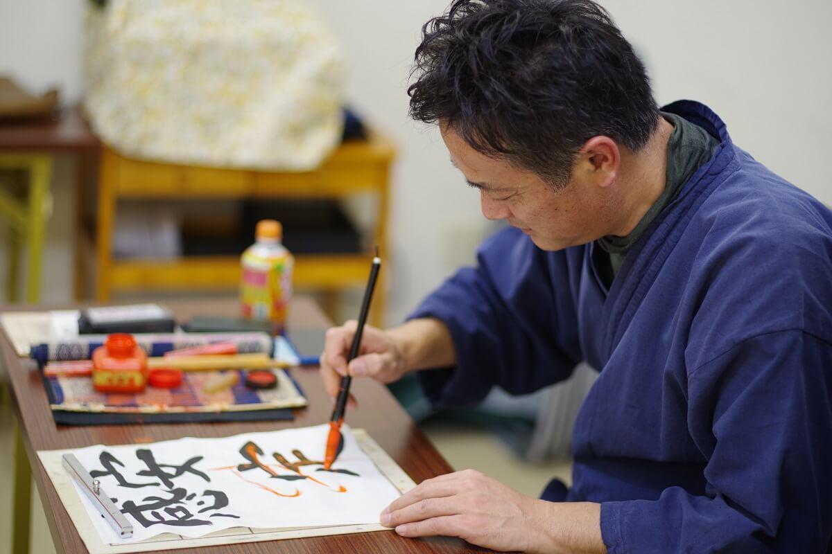 生徒の字に赤を入れる和田華仙氏