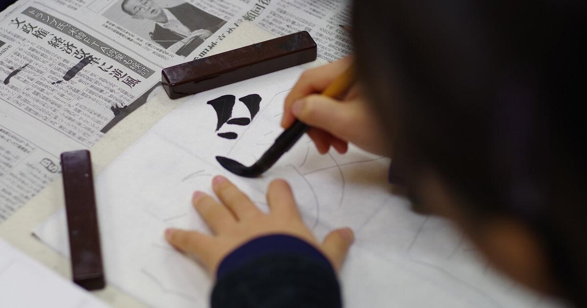 「愛」という字を書いている子ども