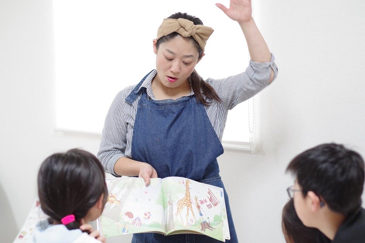 「RK Kitchen」で子どもたちに絵本を見せるRYOKO先生